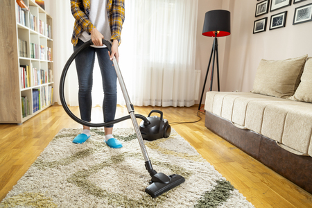 Detail of a young woman doing home chores, vacuuming the living room carpet