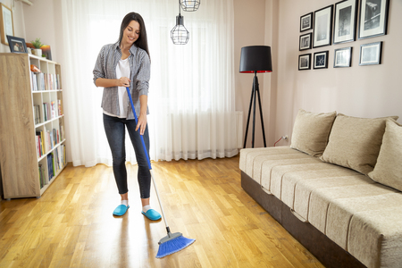Woman doing housework, holding a broom and sweeping the floor Imagens