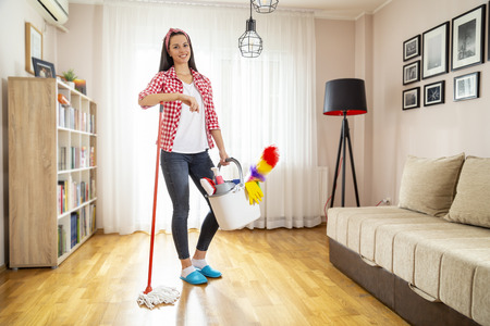 Woman holding a floor wiper and bucket filled with mops and cleaning supplies, doing house work and keeping the daily home hygiene