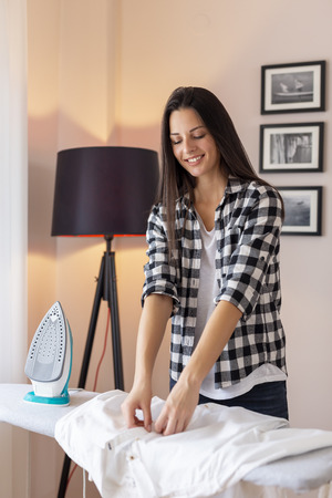 Woman folding clean ironed shirt on the ironing board after doing the ironing Imagens