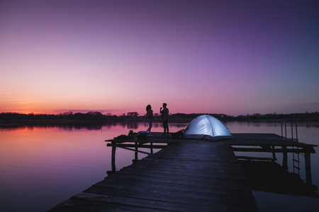 Couple camping on lake docks at dusk, standing next to a tent enjoying beautiful summer night and sky colors right after the sunset