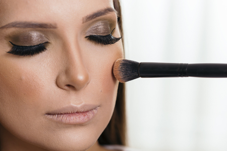 Make up artist doing the models make up, applying the face powder with a make up brush