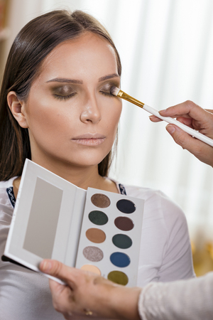 Make up artist working in a make up studio, shading female clients eyelids