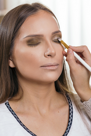Make up artist working in a make up studio, shading the female clients eyelids