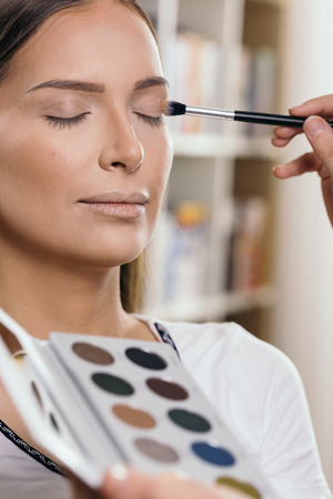 Make up artist working in a make up studio, shading female client's eyelids