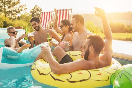 Grupo de amigos en una fiesta de verano junto a la piscina, divirtiéndose en la piscina, bebiendo cócteles y cerveza y haciendo un brindis