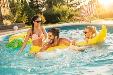 Grupo de amigos en una fiesta de verano junto a la piscina, divirtiéndose en la piscina, salpicando agua y peleando por un colchón flotante