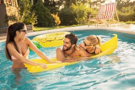 Group of friends at a poolside summertime party,  having fun in the swimming pool, sunbathing on a floating mattress