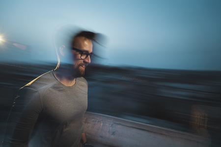 Blured motion, long exposure image of an athletic man walking
