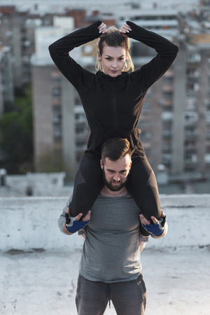 Couple working out on a building rooftop terrace, man carrying woman on his shoulders and doing squats Imagens