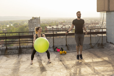 Couple working out on a building rooftop terrace, jumping ropes and doing pilates ball exercises
