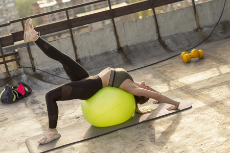 Woman working out with a pilates ball on a building rooftop terrace, doing a backbend