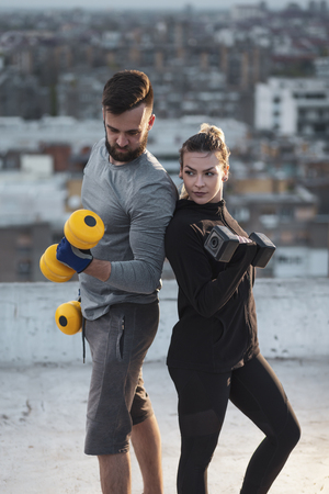 Young couple working out on a building rooftop terrace, lifting weights, doing arms exercises Imagens