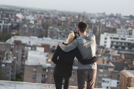 Young couple standing on a building rooftop terrace, hugging and enjoying the view over the city