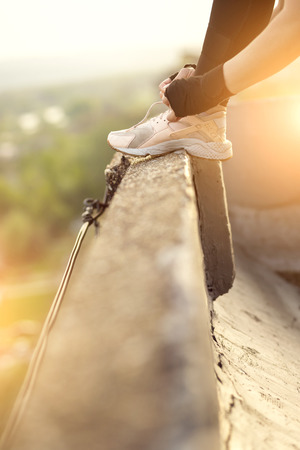 Woman wearing sportswear standing on a building rooftop terrace, tying shoelaces before workout Imagens