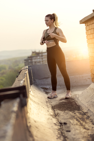 Woman wrapping hands with bandages before workout on a building rooftop terrace Imagens