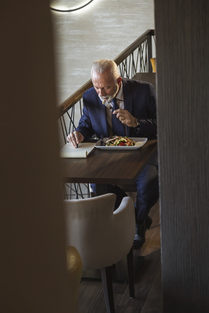 Senior businessman on a lunch break in a restaurant, eating and reading terms of new business contract