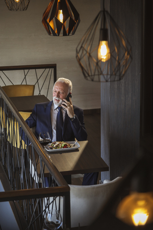 Senior businessman taking a break, having lunch in a restaurant and apeaking on the phone Imagens
