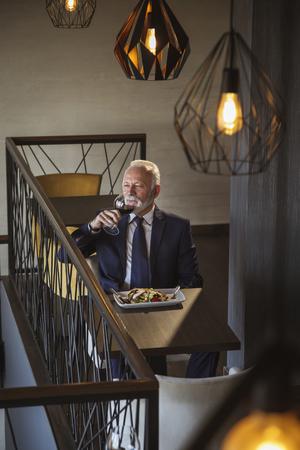 Senior businessman taking a break, tasting wine and having lunch in a restaurant