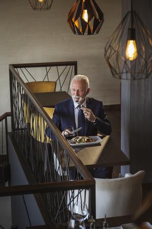 Senior businessman taking a break, having lunch in a restaurant Imagens