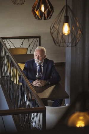 Portrait of a pensive senior businessman sitting in a modern restaurant, drinking wine and looking away from the camera