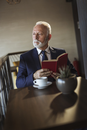 Senior businessman sitting at a restaurant table, reading a book and drinking coffee