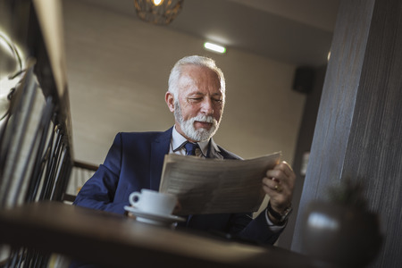 Senior businessman sitting at a restaurant table, reading newspaper and drinking coffee