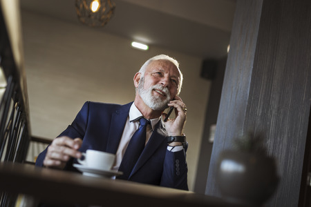 Senior businessman on a coffee break in restaurant, having a phone conversation with business partner and drinking coffee
