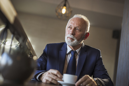 Senior businessman on a meeting in a restaurant, waiting for a business partner and drinking coffee