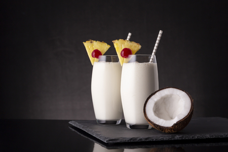 Two glasses of pina colada cocktail with dark rum, pineapple juice and coconut cream, decorated with pineapple slices and maraschino cherry and coconut half