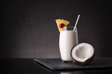 Glass of pina colada cocktail with dark rum, pineapple juice and coconut cream, decorated with pineapple slices, maraschino cherry and coconut half