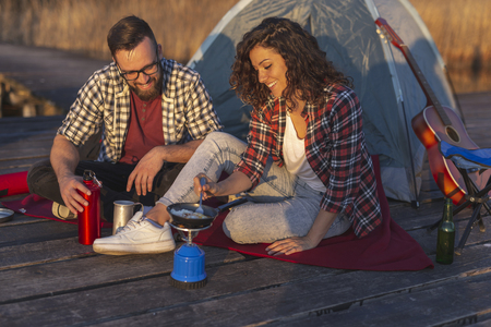 Couple in love on an outdoor camping adventure, preparing a meal at a lake docks and enjoying a beautiful day in nature