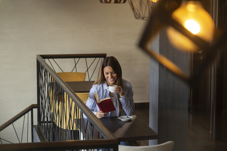 Portrait of a beautiful young woman sitting at a restaurant table, drinking coffee and reading a book