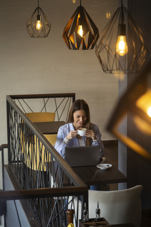 Portrait of a beautiful young woman sitting at a restaurant table, drinking coffee and working on a laptop computer