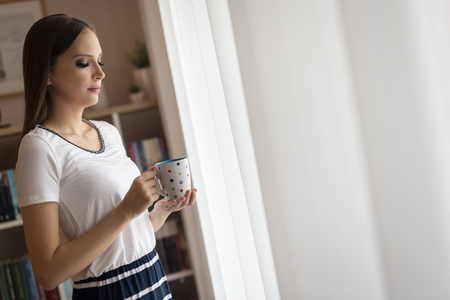 Beautiful young woman standing by the window and having her morning cup of coffee, relaxing and enjoying leisure time Stock fotó