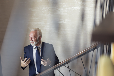 Senior businessman walking up the stairs in a modern office building, speaking to a colleague he met while going to his workplace