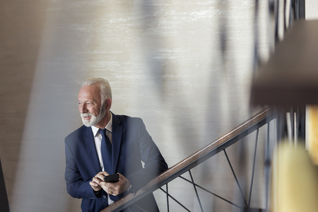 Senior businessman walking up the stairs in a modern office building, going to his workplace, speaking to a colleague and using a smart phone