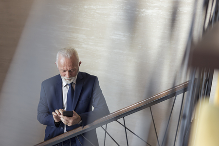 Senior businessman walking up the stairs in a modern office building, going to his workplace and typing a text message