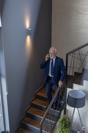 Senior businessman walking down the modern office building stairway, having a phone conversation while leaving the office