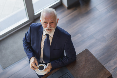 High angle view portrait of a senior businessman standing by a restaurant counter, drinking coffee and working on a laptop computer 版權商用圖片