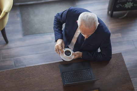 High angle view portrait of a senior businessman standing by a restaurant counter, drinking coffee and working on a laptop computer Stock fotó