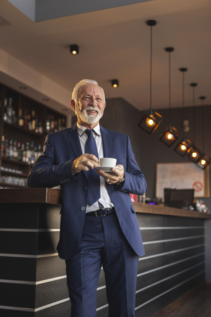Portrait of a senior businessman standing next to a restaurant counter, having a cup of coffee