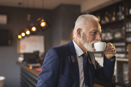 Senior businessman having a cup of coffee in a modern office building cafeteria
