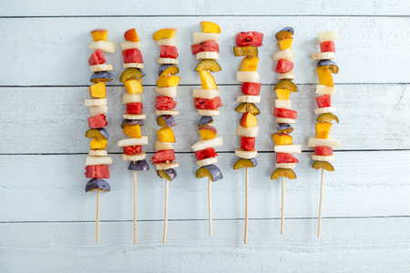 Top view of a cold colorful mixed fruit salad served on barbecue sticks as a summertime dessert