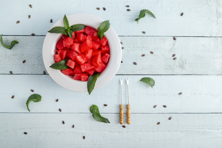 Table top shot of a bowl of watermelon slices on a light blue rustic background decorated with watermelon seeds and mint leaves
