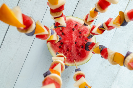 Table top shot of a colorful mixed seasonal fruit salad served on barbecue sticks, stuck in a watermelon half as a summer party dessert