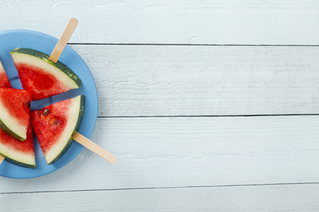 Table top shot of watermelon popsicles on a plate on rustic light blue wooden table