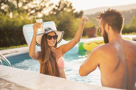 Couple in love at a poolside summer party, standing in water next to the swimming pool edge, drinking beer and having fun