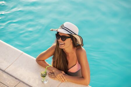 Attractive young woman wearing bikini, sunglasses and a hat, standing in the swimming pool leaning on the edge, drinking cocktails and sunbathing