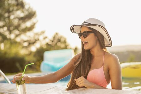 Attractive young woman wearing bikini, sunglasses and a hat, drinking cocktails by the swimming pool edge and having fun Stock fotó